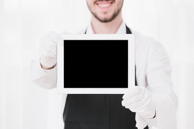 Смайлик официант показывает макет планшета