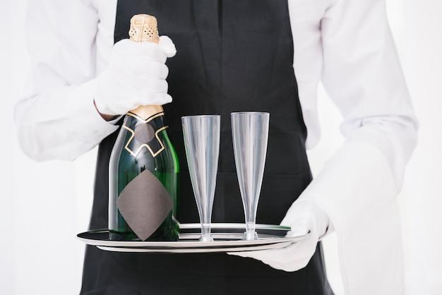 Официант в форме держит бутылку с бокалами