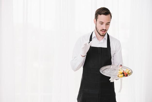 Удивленный официант держит тарелку