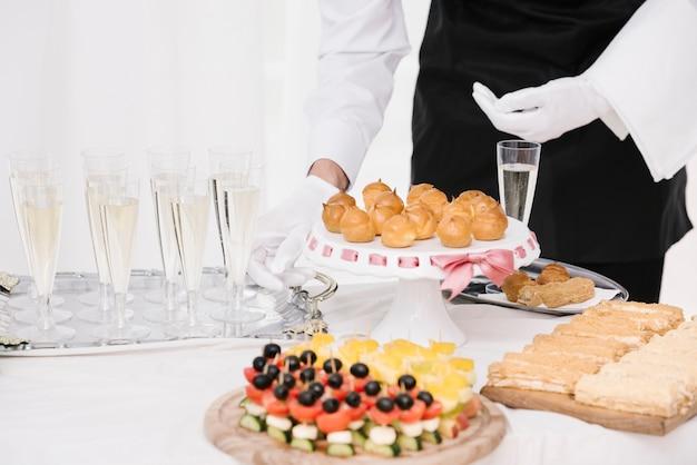 Официант, представляя смесь еды и напитков на столе