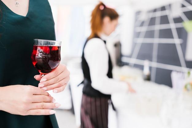 アルコールとガラスを保持している女性