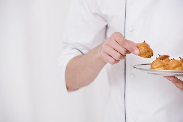 Шеф-повар держит тарелку с безе