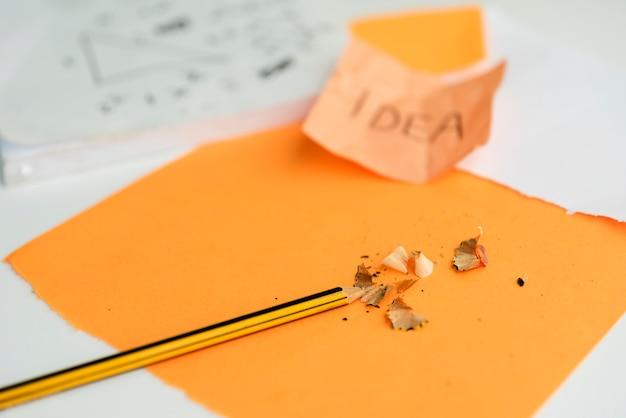 鉛筆とオレンジ色の紙の上に剃る鉛筆のクローズアップ