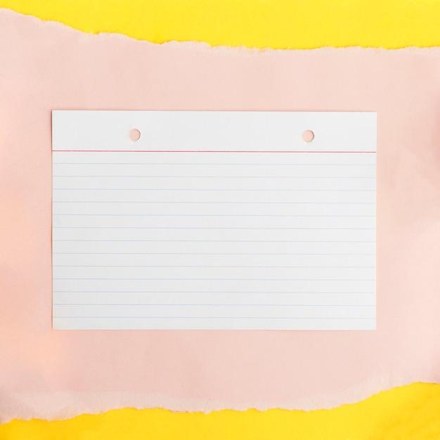 黄色の背景の上のベージュのカード紙のテクスチャライン紙