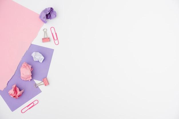 しわくちゃの紙と白い背景の上の色のカード紙とクリップ