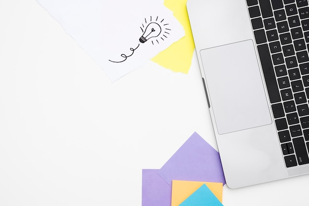 白い机の上のノートパソコンと色のクラフトペーパーの立面図