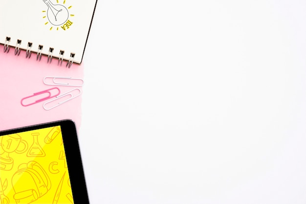 白い背景の上のデジタルタブレットとスパイラルメモ帳にアイデアテキストと手描き電球