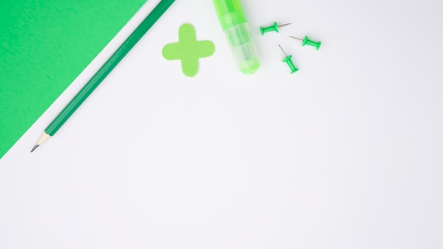Зеленая крафт-бумага; карандаш; клей и толкатель над белой поверхностью