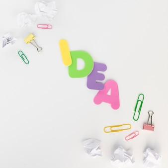 しわくちゃの紙でカラフルなアイデアのテキスト文字とペーパークリップ