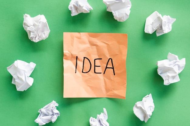 緑の背景のアイデアテキストとオレンジ色の粘着メモで紙をくしゃくしゃ