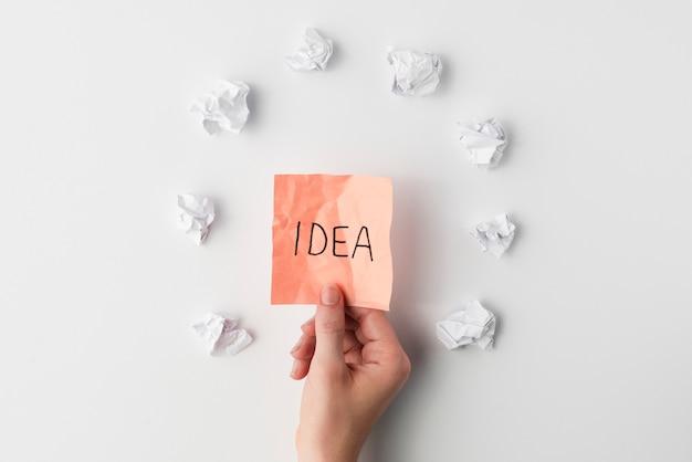 白い背景の上のしわくちゃの紙に囲まれたアイデアテキスト付きの付箋を持っている人間の手の平面図