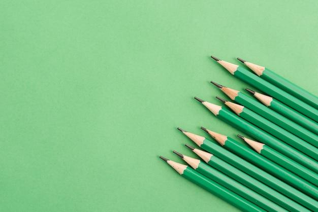 無地の背景の隅にシャープな緑色の鉛筆