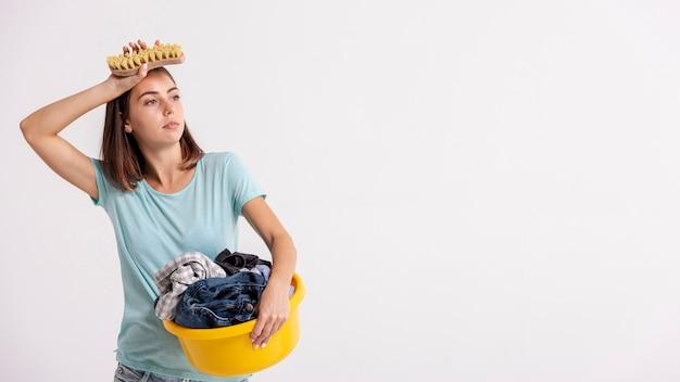 Среднего выстрела утомленная женщина с щеткой и корзиной для белья