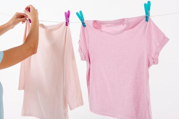 Женщина фиксирует футболки на бельевой веревке с прищепками
