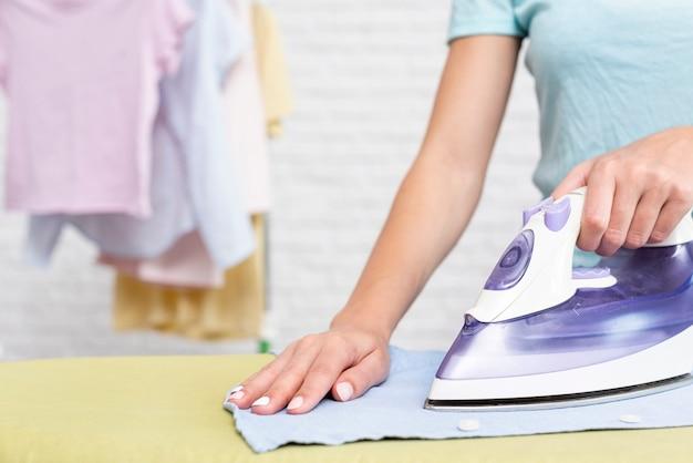 Крупным планом женщина гладит одежду