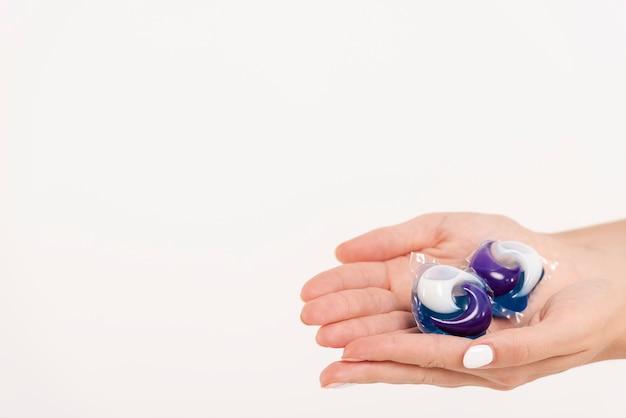 Крупным планом женщина, держащая стиральные таблетки
