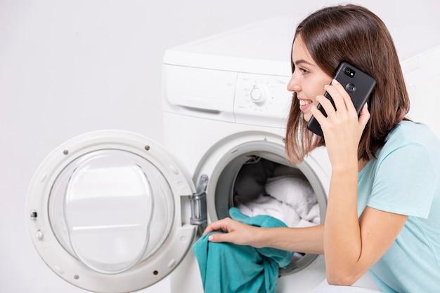 Женщина разговаривает по телефону во время стирки
