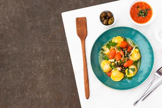 トマトソースとテーブルの上のオリーブのおいしいラビオリパスタ