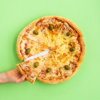 緑の背景にピザのスライスを持っている女性の手の高角度のビュー