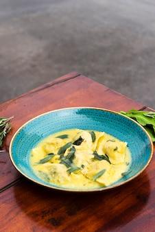 パルメザンチーズと木製のテーブルの上のプレートにバジルのおいしいラビオリパスタ飾り