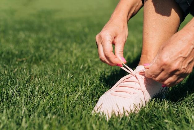 Крупным планом женщина, связывая ее шнурки