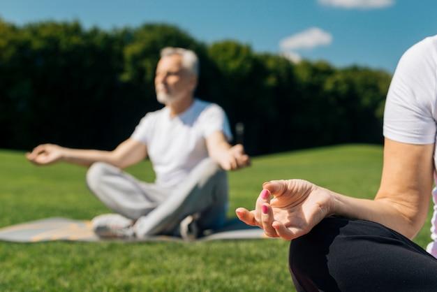 Крупным планом люди медитируют на открытом воздухе