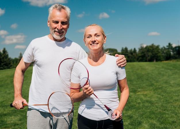 テニスラケットでポーズ正面のカップル