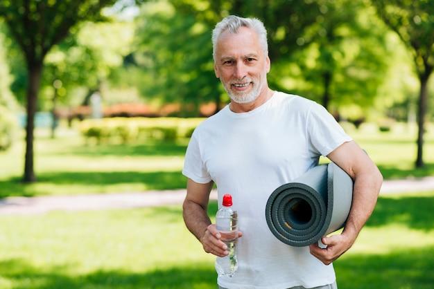 水のボトルとマットを持つミディアムショット男