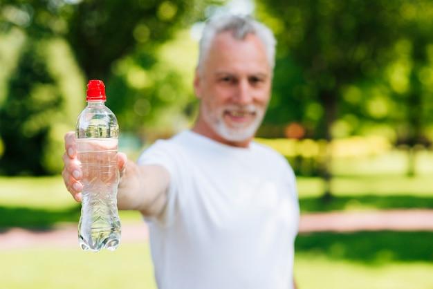 水のボトルを保持しているミディアムショット男