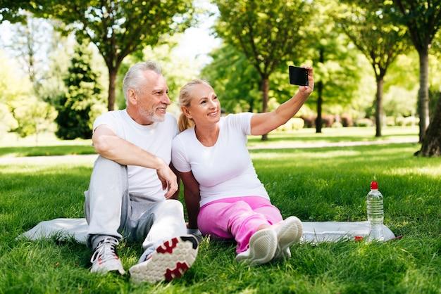 Полный снимок счастливых людей, принимающих селфи на открытом воздухе
