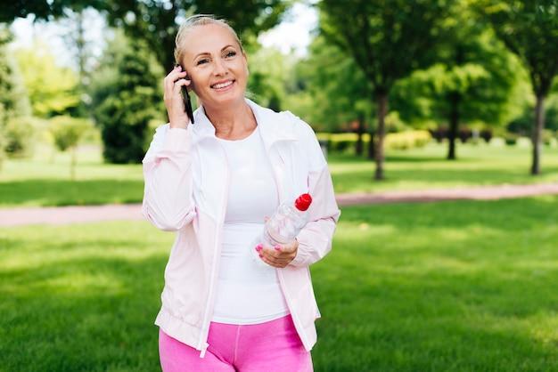 Средний выстрел женщина разговаривает по телефону