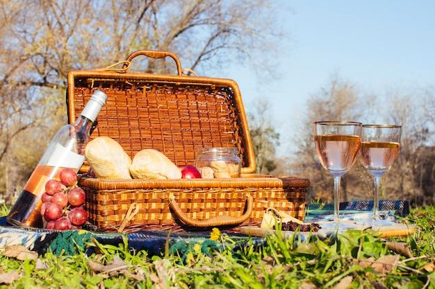 ピクニックバスケットの横にあるワイングラス