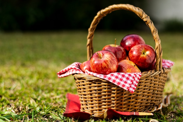 Вкусные красные яблоки в соломенной корзине