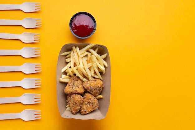 不健康な食べ物やフォークとフラットレイアウトの配置