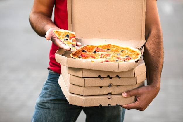 Парень доставки крупным планом, держа кусок пиццы