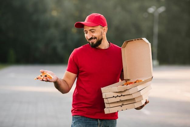 Парень с доставкой среднего выстрела смотрит на кусок пиццы