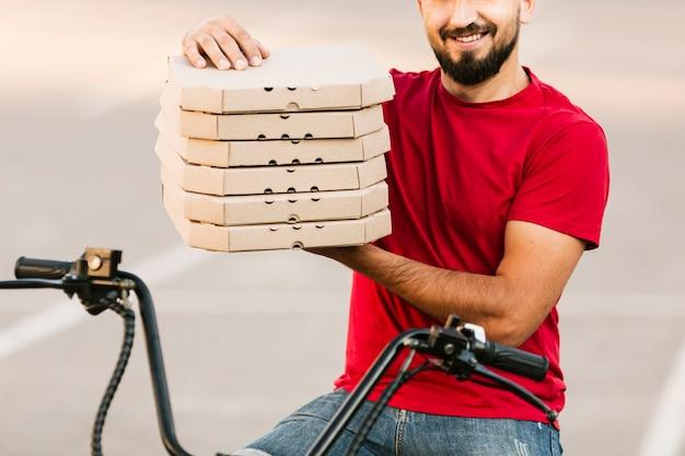 Крупный план доставки человек, держащий коробки для пиццы
