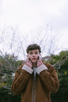 自然の中でジャケットを配置する若い男
