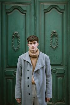 ロングコートを持つ若い男