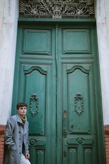 大きな正面玄関の近くの少年