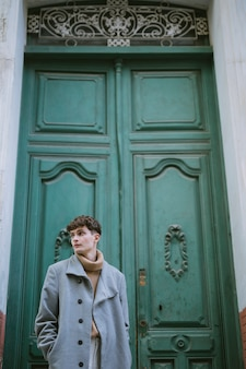 玄関でコートを持つ少年