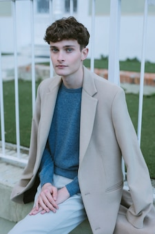 肩にコートを持つ若い男
