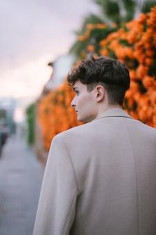花の近くを歩く若い男の後ろ