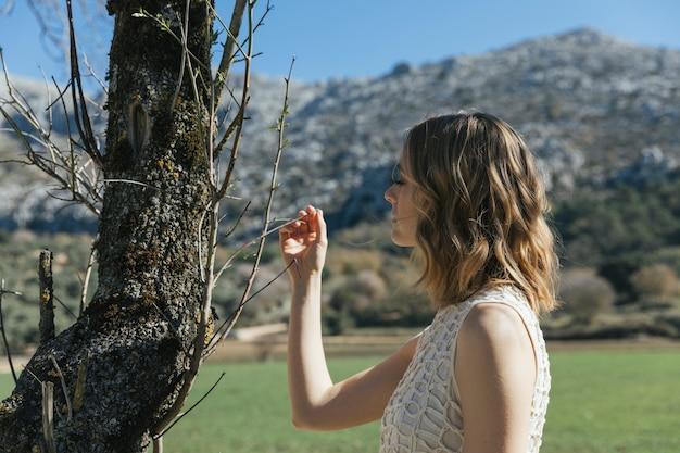 小さな枝を見て若い女性