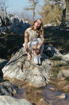 岩の上に座っているロングショット女性
