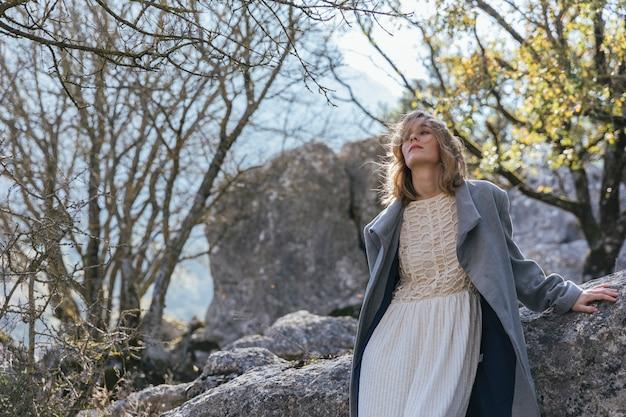 岩の上の手でミディアムショット女性