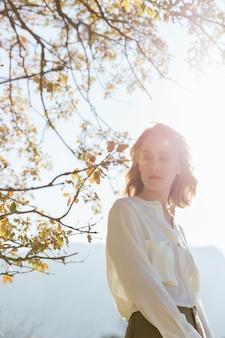 日光の下で見つめている若い女性