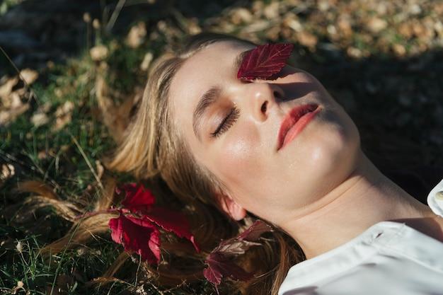 目の上の葉を持つ女性の明るい顔