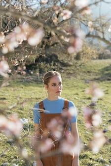 開花枝の間の若い女性