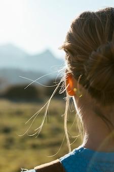 太陽に直面して後ろから若い女性